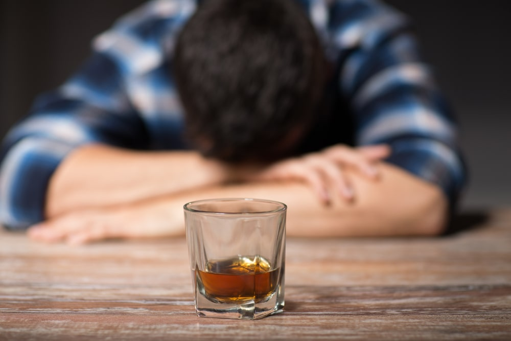 An Alcoholic drink with a person slumped over